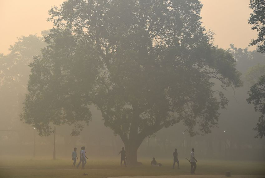 TOPSHOT - Indian men play cricket amid heavy smog in New Delhi on October 20, 2017 the day after the Diwali Festival. New Delhi was shrouded in a thick blanket of toxic smog a day after millions of Indians lit firecrackers to mark the Diwali Festival. / AFP PHOTO / DOMINIQUE FAGET        (Photo credit should read DOMINIQUE FAGET/AFP/Getty Images)