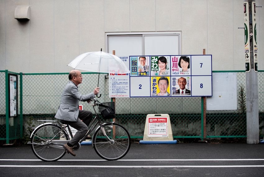 TOPSHOT - A man walks past electoral posters of Japanese candidates for the upcoming general election in Koshigaya city, Saitama prefecture, on October 20, 2017. A typhoon is expected to lash Japan with heavy rains on October 22, potentially weighing on turnout as millions of voters head to the polls in the world's third-biggest economy. / AFP PHOTO / Behrouz MEHRI        (Photo credit should read BEHROUZ MEHRI/AFP/Getty Images)
