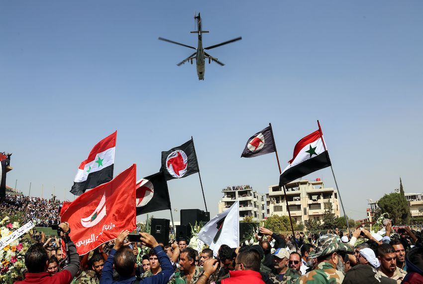 TOPSHOT - Syrians wave their national flags and those of the Syrian Social Nationalist Party in a stadium as a Russian-made Mil Mi-24 helicopter gunship hovers above during the funeral for Brigadier General Issam Zahreddine, in the southern city of Suwaida on October 20, 2017. Zahreddine, accused over the 2012 deaths of prominent US journalist Marie Colvin and French photographer Remi Ochlik, was reportedly killed by an explosion in the eastern city of Deir Ezzor on October 18, where Russian-backed regime forces are battling the Islamic State group, was reported by pro-regime media in Damascus. / AFP PHOTO / STRINGER        (Photo credit should read STRINGER/AFP/Getty Images)