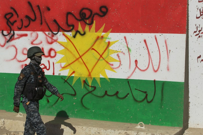 A member of the Iraqi security forces walks past a defaced Kurdish flag on the outskirts of Kirkuk on Oct. 16. (AHMAD AL-RUBAYE/AFP/Getty Images)