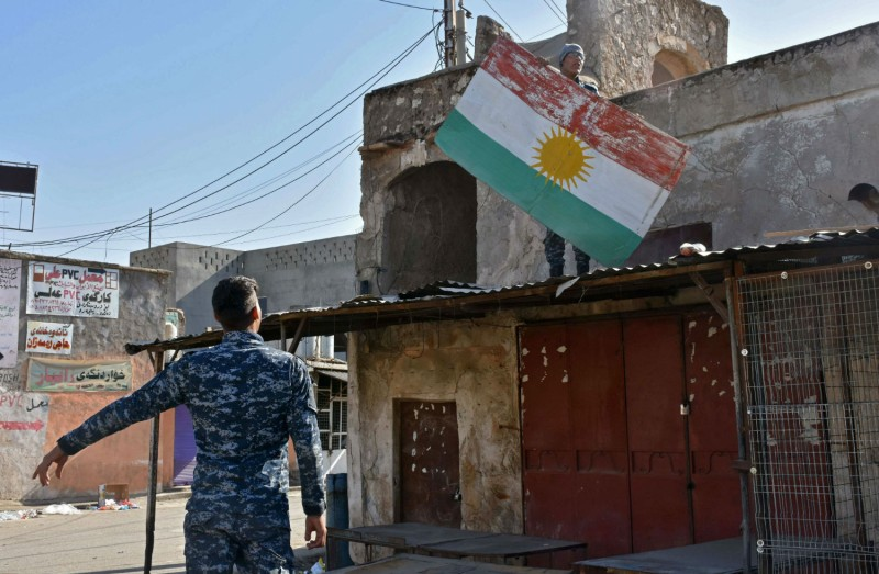 Iraqi fighters tear down a sign painted with the colors of the Kurdish flag in northern Iraq on Oct. 20. (Marwan Ibrahim/AFP/Getty Images)