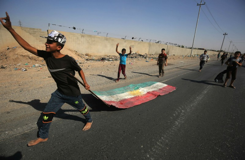 An Iraqi boy drags a Kurdish flag as Iraqi forces advance toward the center of Kirkuk on Oct. 16. (Ahmad al-Rubaye/AFP/Getty Images)