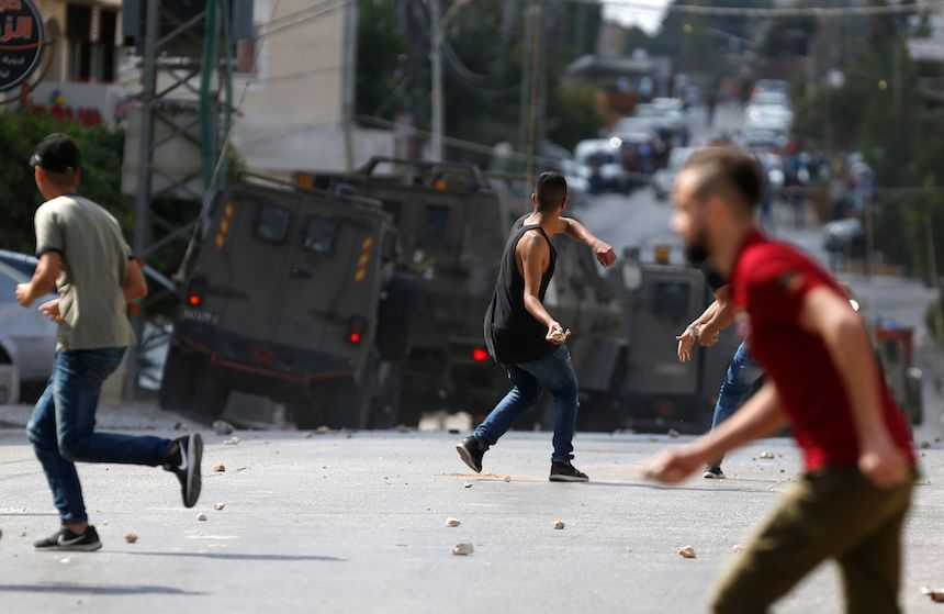 Palestinian protestors throw rocks at Israeli security forces after the Israeli army entered and searched some buildings in the West Bank city of Ramallah on October 6. / AFP PHOTO / ABBAS MOMANI        (Photo credit should read ABBAS MOMANI/AFP/Getty Images)