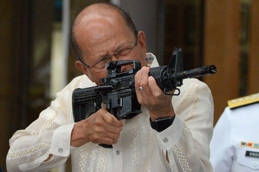 Philippine Defense Secretary Delfin Lorenzana points a CQ-A5b (M4) rifle donated by the Chinese government in Manila on October, 5.  China turned over 3,000 assault rifles, which, along with ammunition and light scopes amounted to 3.2 million USD for use in fighting terrorism. TED ALJIBE/AFP/Getty Images)