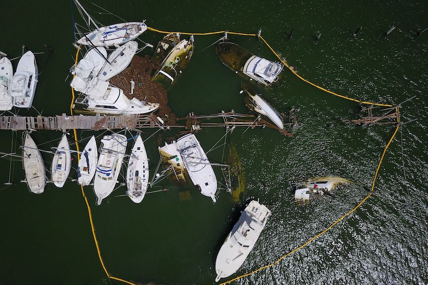 Oil spill containment barriers surround damaged boats affected by the passing of Hurricane Maria in Fajardo, Puerto Rico on October 4. (RICARDO ARDUENGO/AFP/Getty Images)
