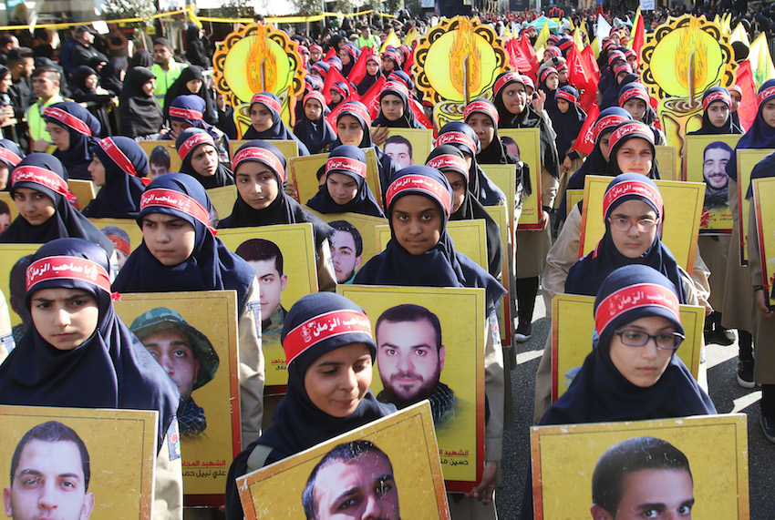 Members of Lebanon's Shiite Hezbollah scout movement hold portraits of Hezbollah fighters killed while fighting in Syria during a procession following the mourning period of Ashura in the southern Lebanese city of Nabatieh on October 4, 2017.        (MAHMOUD ZAYYAT/AFP/Getty Images)