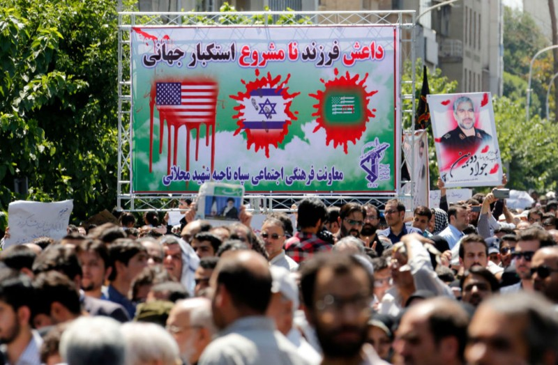 Iranians hold posters condemning the United States, Israel, and Saudi Arabia at the funeral of the victims of terror attacks on Tehran's parliament complex and the shrine of Ayatollah Ruhollah Khomeini on June 9. (Atta Kenare/AFP/Getty Images)