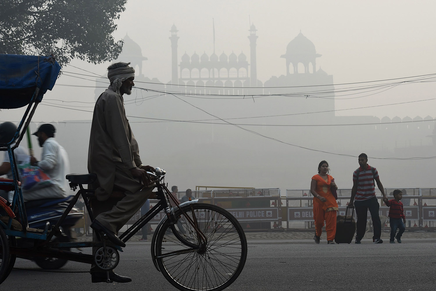 An Indian family crosses a road amid heavy smog in front of the Red Fort in New Delhi on Nov. 10.   should read Prakash Singh/AFP/Getty Images
