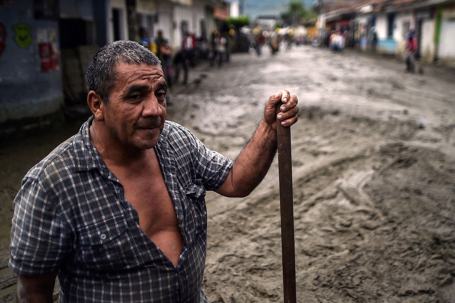 A man stands amid a muddy street after a mudslide due to heavy rains affected Corinto in Cauca department, southwest Colombia on Nov. 8. Luis Robayo/AFP/Getty Images