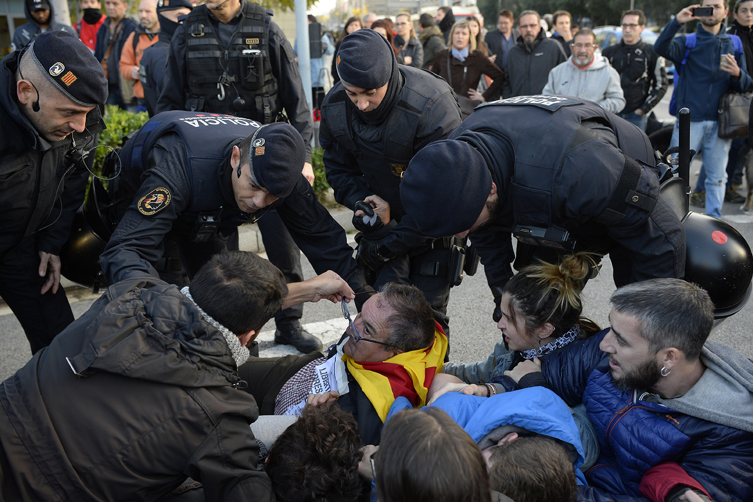 Catalan regional policemen (Mossos d'Esquadra) talk to picketers blocking the street at the Placa Cerda square in Barcelona during a general strike to protest the jailing of eight sacked regional lawmakers on Nov. 8.  Josep Lago/AFP/Getty Images