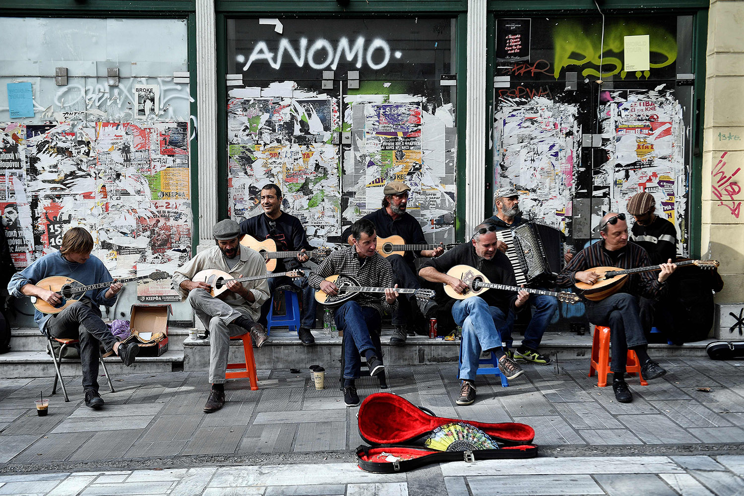 Musicians play Greek traditional music with Bouzoukis (front), guitars and an accordion in front of closed down stores in central Athens on Nov. 9. Louisa Gouliamaki/AFP/Getty Images