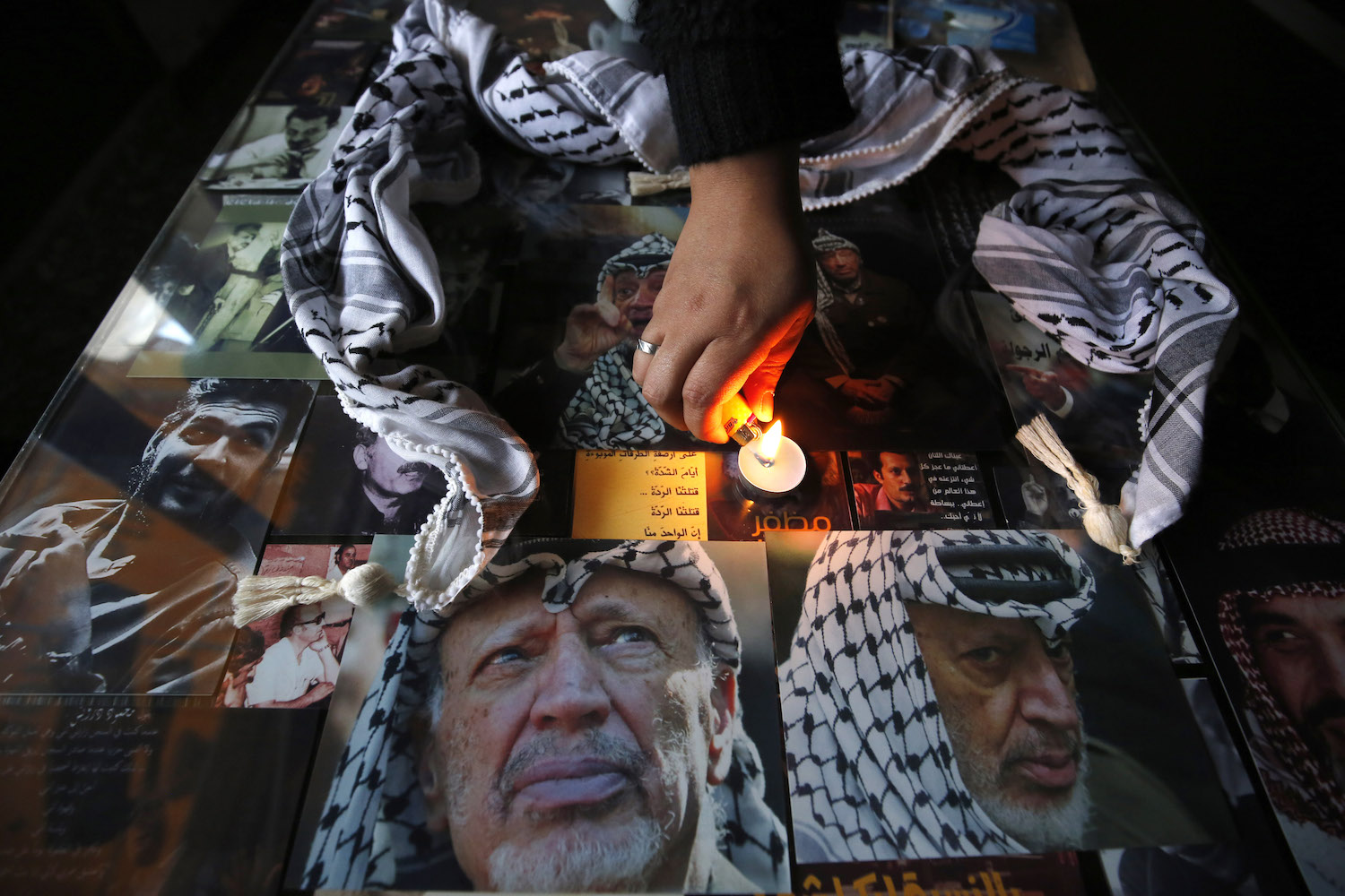 A Palestinian woman lights a candle over portraits of late leader Yasser Arafat at the start of celebrations marking the 13th anniversary of his death, in the West Bank city of Ramallah, on Nov. 9.      Abbas Momani/AFP/Getty Images