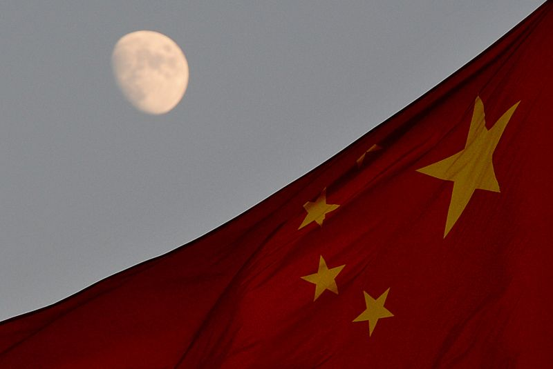 The Chinese flag flies before a rising moon at Tiananmen Square in Beijing on Dec. 13, 2013.  (Mark Ralston/AFP/Getty Images)