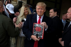 Donald Trump holds a copy of Time Magazine outside the John Wayne Birthplace Museum in Winterset, Iowa, on Jan. 19, 2016. (Aron P. Bernstein/Getty Images)