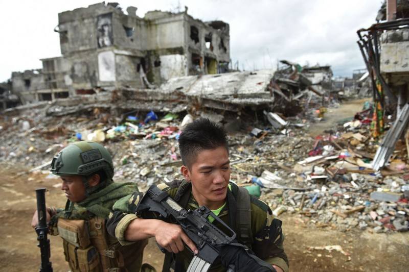 Government troops keep watch as bombed-out buildings are seen in what was the main battle area in Marawi on the southern island of Mindanao on Oct. 25, days after the military declared the fighting against IS-inspired Muslim militants over. (Ted Aljibe/AFP/Getty Images)