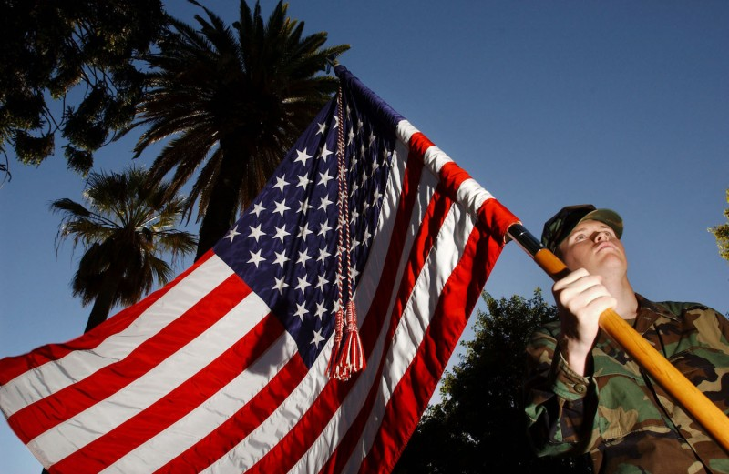 Brian Jones, of Orange High School ROTC, holds an American flag on color guard duty during a Veterans Day observance Nov. 11, 2002 in Orange, California. (David McNew/Getty Images)