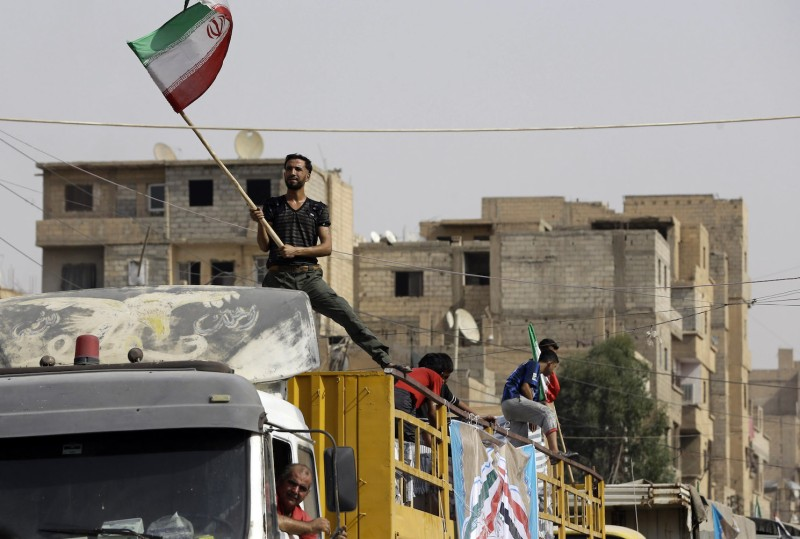A Syrian man holds the Iranian flag as a convoy carrying aid provided by Iran arrives in the eastern city of Deir Ezzor on Sept. 20. (Louai Beshara/AFP/Getty Images)