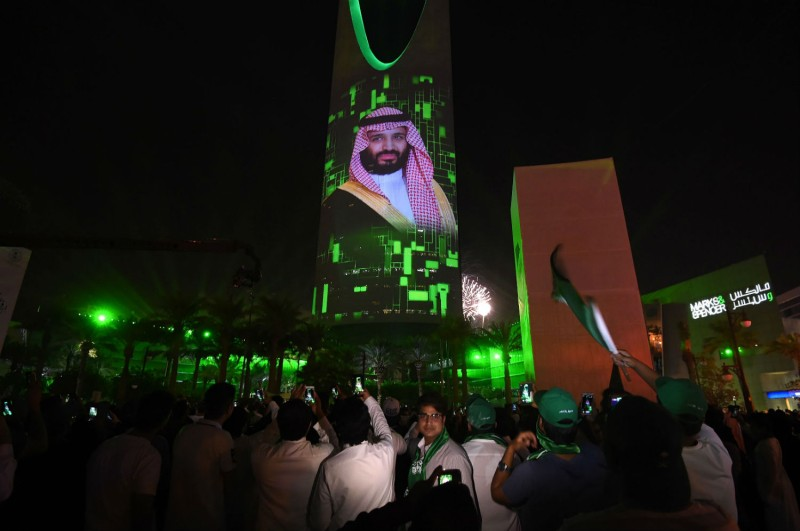 People in Riyadh watch a projection depicting a portrait of Crown Prince Mohammed bin Salman during an event on Sept. 23 commemorating the anniversary of the kingdom's founding. (/AFP/Getty Images)