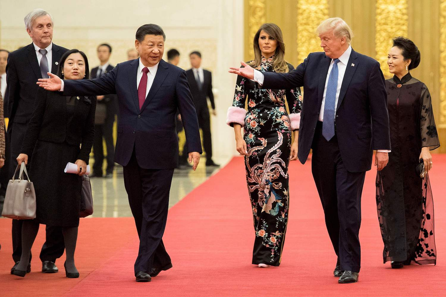 U.S. President Donald Trump (second right) gestures toward China's President Xi Jinping (third left), as U.S. First Lady Melania Trump (center) and Xi's wife Peng Liyuan (right) look on, the Great Hall of the People in Beijing on Nov. 9. Jim Watson/AFP/Getty Images