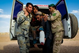 Various members of the Afghan armed forces unload a casualty from an ambulance at the Tirinkot airbase in Uruzgan province on May 4.