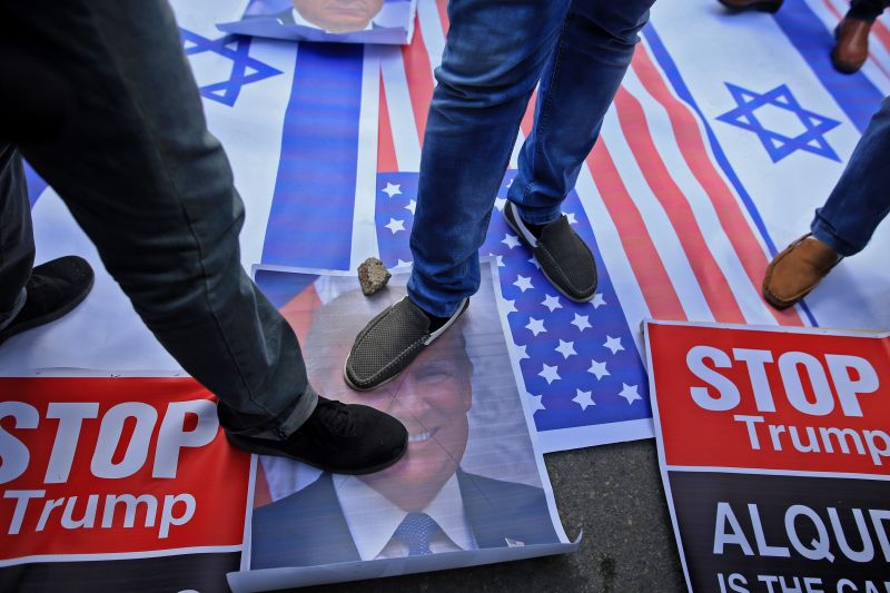 Palestinian protesters step on US and Israeli flags and on a portrait of President Donald Trump in Gaza City, on December 7.  (Mohammed Abed)