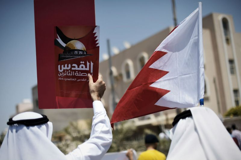 "Bahraini men hold up a national flag and a placard reading in Arabic ""Jerusalem is the compass of the revolutionaries"" during a demonstration in the village of Diraz on July 10, 2015. (Mohammed al-Shaikh/AFP/Getty Images)"