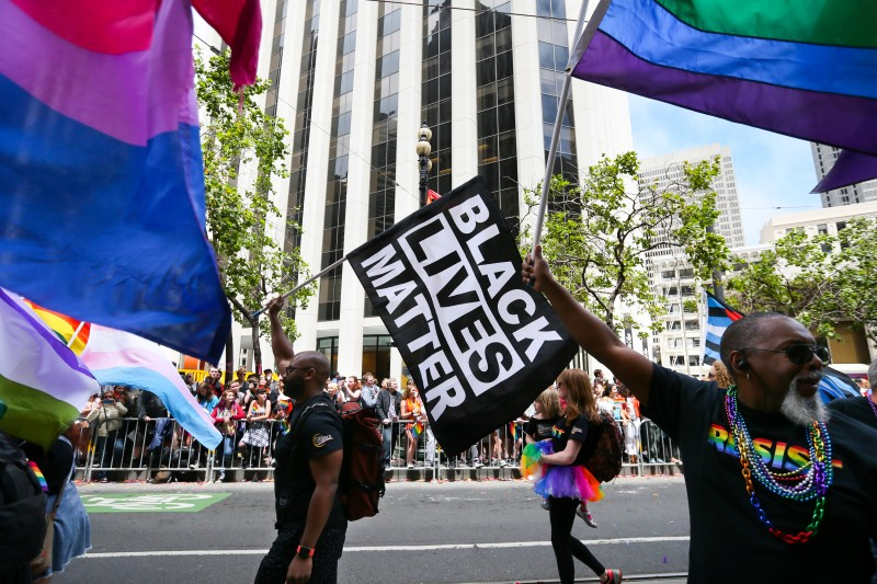 Men wave rainbow and 'black lives matter' flags while marching in the annual LGBTQI Pride Parade on June 25, 2017 in San Francisco. (Elijah Nouvelage/Getty Images)