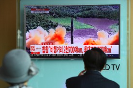 TOPSHOT - People watch a television news screen showing file footage of a North Korean missile launch, at a railway station in Seoul on August 29, 2017. Nuclear-armed North Korea fired a ballistic missile over Japan and into the Pacific Ocean on August 29 in a major escalation by Pyongyang amid tensions over its weapons ambitions. / AFP PHOTO / JUNG Yeon-Je        (Photo credit should read JUNG YEON-JE/AFP/Getty Images)