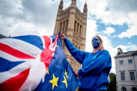 A pro-European Union protester holds U.K. and European flags in front of Victoria Tower at the Palace of Westminster in central London on Sept. 13, 2017. (Tolga Akmen/AFP/Getty Images)