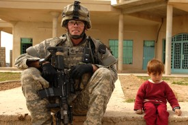 U.S. Army Staff Sgt. Christopher Pearce sits next to a young boy during a visit to Shiek Burhan Al Asee's house during a patrol of the Riyahd village in Iraq on March 8, 2007. (U.S. Air Force photo by Master Sgt. Andy Dunaway)