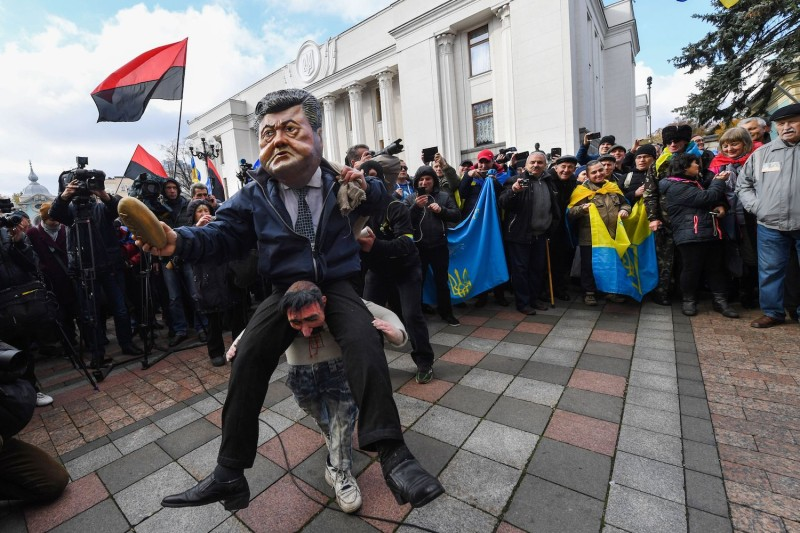 An activist wears a mask depicting Ukraine's President during an opposition rally in front of the Ukrainian parliament in Kiev on October 22. (Sergei Supinsky/AFP/Getty Images)