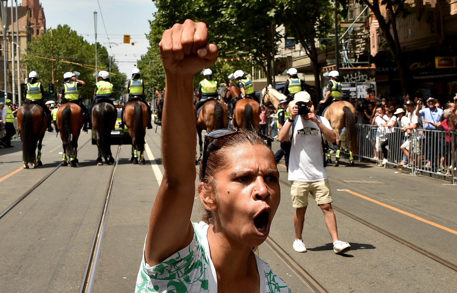 "A protester gestures during an ""Invasion Day"" rally on Australia Day in Melbourne on Jan. 26, 2018.  Tens of thousands of people marched across Australia on January 26 in an ""Invasion Day"" protest calling for a rethink of the national day they say is offensive to indigenous people.  / AFP PHOTO / Peter PARKS        (Photo credit should read PETER PARKS/AFP/Getty Images)"