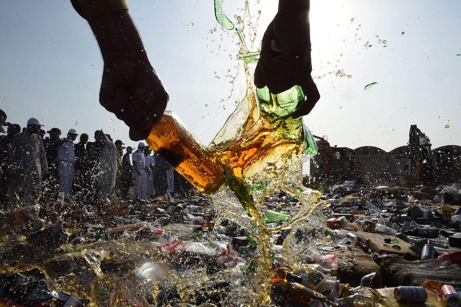 A Pakistani customs official smashes bottles of liquor in Karachi on Jan. 26, during a ceremony on the occasion of the International Customs Day.  Pakistani Customs Collectorate destroyed hundreds of illicit liquor bottles and drugs smuggled into the country. / AFP PHOTO / ASIF HASSAN        (Photo credit should read ASIF HASSAN/AFP/Getty Images)