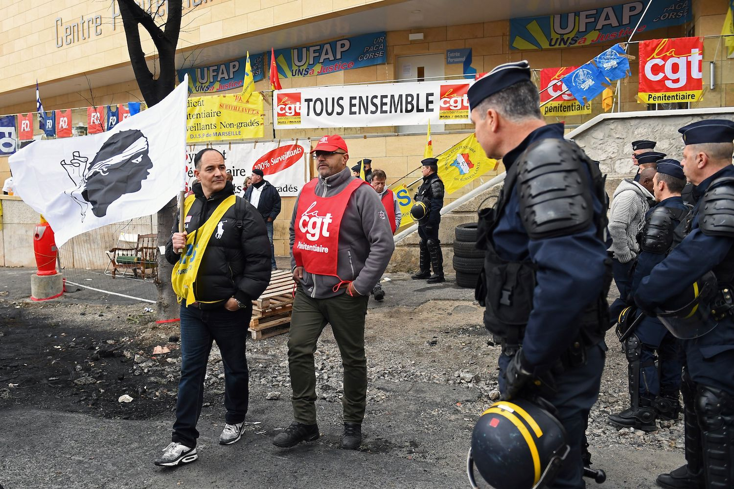 French gendarmes arrive to clear the access to the Baumettes Prison (Centre penitentiaire de Marseille) as a participant holds the Corsican flag during a demonstration of prison officers in front of the prison in Marseille, southern France, on January 25, 2018, as part of a nationwide movement to call for better safety and wages.   / AFP PHOTO / BORIS HORVAT        (Photo credit should read BORIS HORVAT/AFP/Getty Images)
