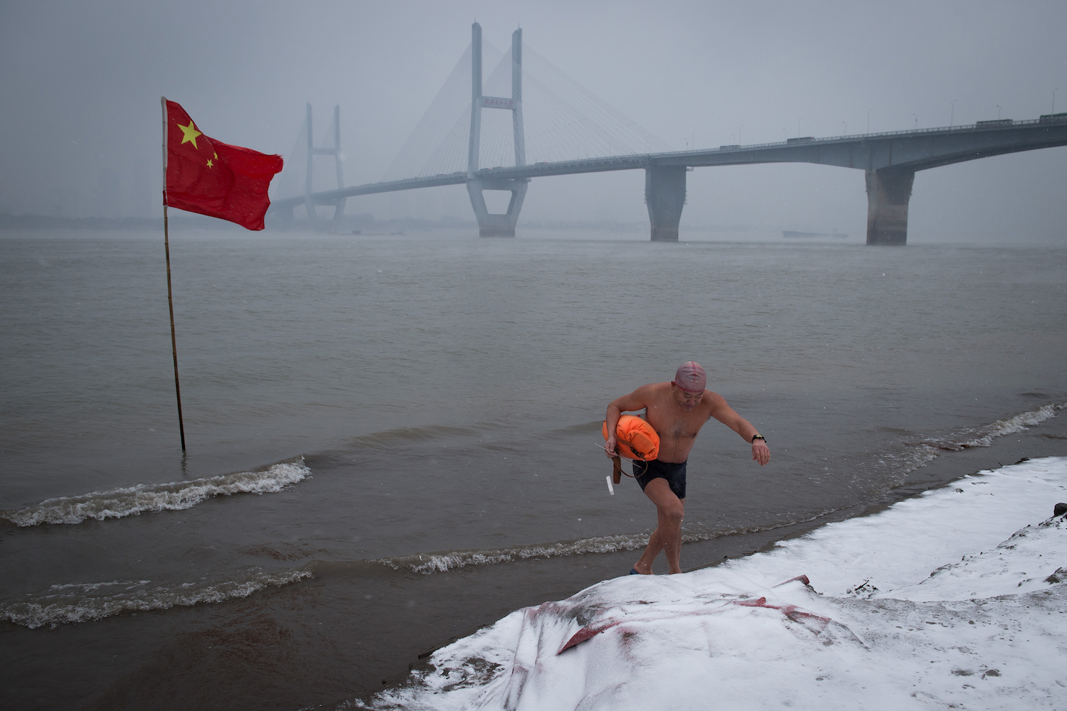 A man walks up the snow-covered bank of the Yangtze river after a swim in Wuhan, in China's central Hubei province on Jan. 25. China's central and eastern provinces have been hit by heavy snowfalls in recent days, causing disruptions to flight and train schedules. / AFP PHOTO / - / China OUT        (Photo credit should read -/AFP/Getty Images)