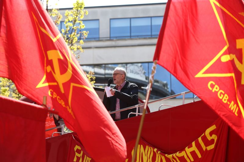 Britain's opposition Labour Party leader Jeremy Corbyn gives a speech from the top of a double-decker bus as Communist Party of Great Britain flags fly at a May Day rally in London on May 1, 2016.