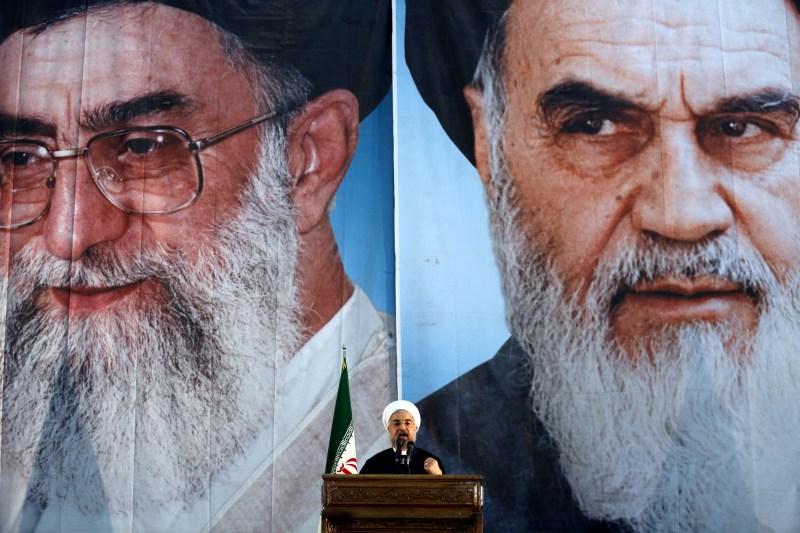 Iranian President Hassan Rouhani under portraits of Ayatollah Ali Khamenei and Ayatollah Ruhollah Khomeini in a suburb of Tehran on June 3, 2014. (Atta Kenare/AFP/Getty Images)