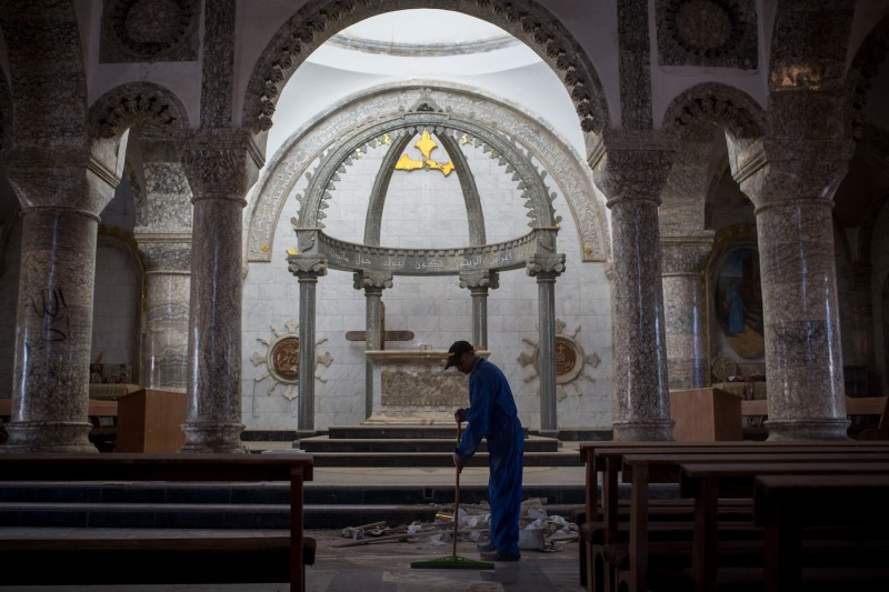A man sweeps up rubble in preparation for Christmas Day mass at the Mar Hanna Church near Mosul, Iraq, on Dec. 22, 2016. (Chris McGrath/Getty Images)