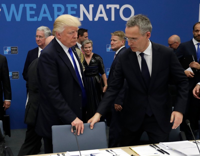 NATO Secretary-General Jens Stoltenberg and U.S. President Donald Trump take seats at a working dinner at NATO headquarters in Brussels on May 25, 2017. (Matt Dunham/AFP/Getty Images)