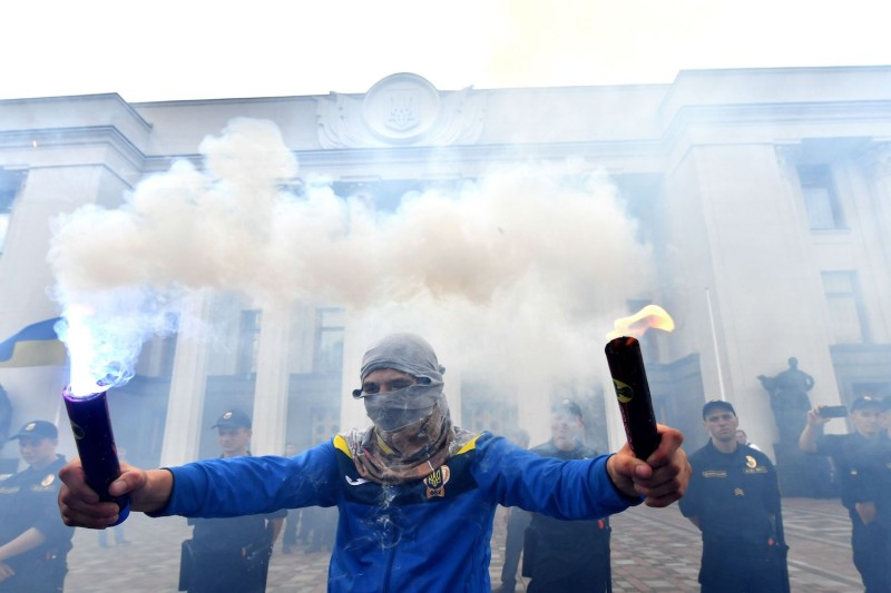 An activists hold up flares during an anti-corruption protest in front of the Ukrainian parliament in Kiev, on July 11, 2017. (Sergei Supinsky/AFP/Getty Images)