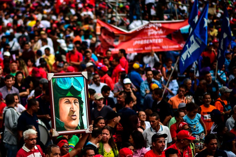 A pro-government activist holds a portrait of late Venezuelan President Hugo Chávez, during a demonstration on Aug. 14, 2017. (Ronaldo Schemidt/AFP/Getty Images)