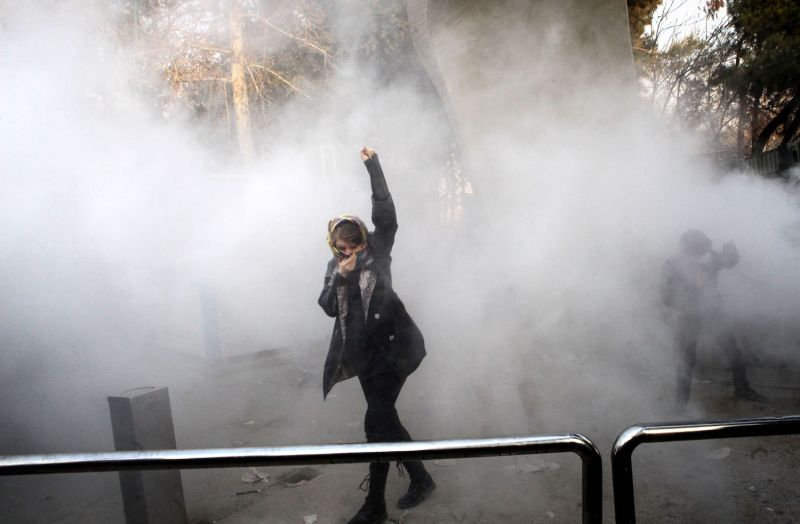 An Iranian woman raises her fist amid tear gas smoke during a protest at the University of Tehran on Dec. 30, 2017. (Stringer/AFP/Getty Images)