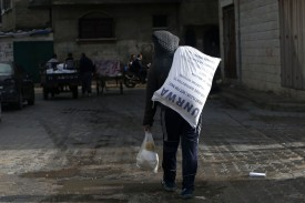 A Palestinian child carries UNRWA food donations outside a U.N. food distribution center in Gaza City on Jan. 15, 2018. (Mohammed Abed/AFP/Getty Images)