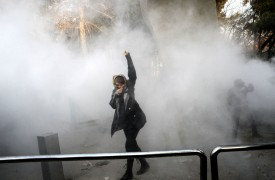 An Iranian woman raises her fist amidst the smoke of tear gas at the University of Tehran during a protest in Tehran on Dec. 30, 2017. (STR/AFP/Getty Images)