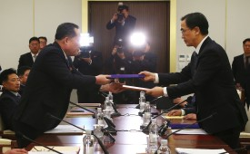 South Korea's Unification Minister Cho Myung-Gyun (right) and North Korean chief delegate Ri Son-Gwon exchange joint statements during their meeting at the border truce village of Panmunjom in the Demilitarized Zone (DMZ) dividing the two Koreas on Jan. 9.(/AFP/Getty Images)