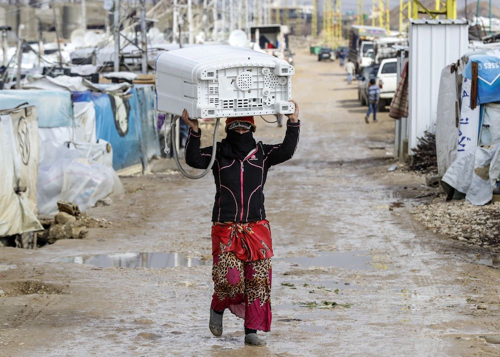 A Syrian woman carries a washing machine above her head as she walks down through the tents and shelters at a refugee camp on the outskirts of the town of Zahle in Lebanon's Bekaa Valley on Jan. 26.  Lebanon, a country of four million, hosts just under a million Syrians who have sought refuge from the war raging in their neighbouring homeland since 2011, many of whom live in informal tented settlements in the country's east and struggle to stay warm in the winter. / AFP PHOTO / JOSEPH EID        (Photo credit should read JOSEPH EID/AFP/Getty Images)