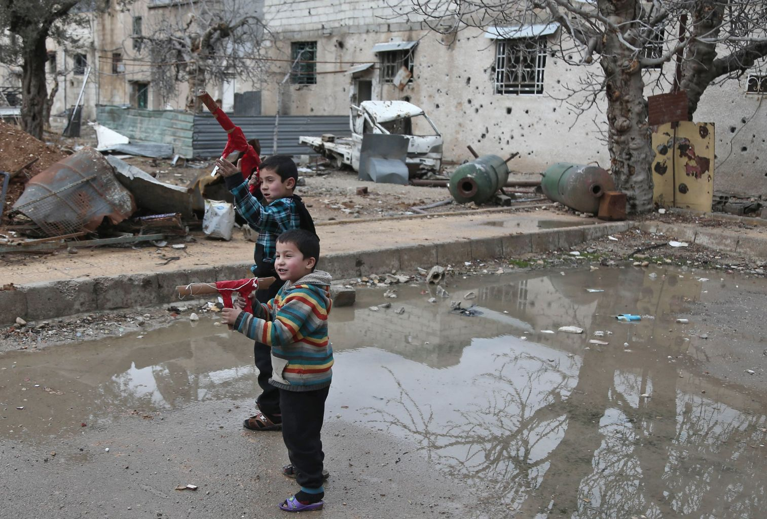 Syrian children play with cardboard guns in the rebel-held town of Harasta, in the Eastern Ghouta region on the outskirts of Damascus on January 25, 2018. / AFP PHOTO / ABDULMONAM EASSA        (Photo credit should read ABDULMONAM EASSA/AFP/Getty Images)