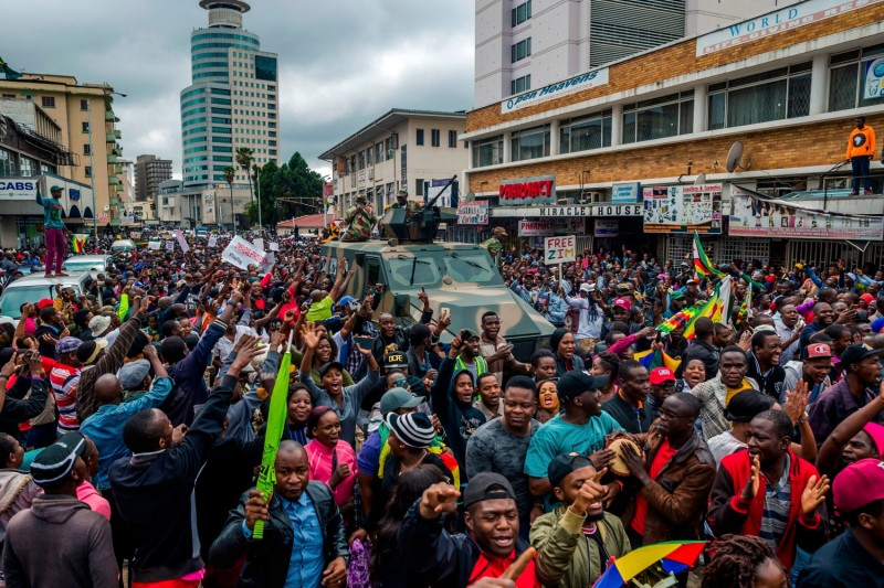 Protesters in the Zimbabwean capital of Harare cheer a military vehicle during a demonstration demanding President Robert Mugabe's resignation on Nov. 18. (Jekesai Njikizana/AFP/Getty Images)