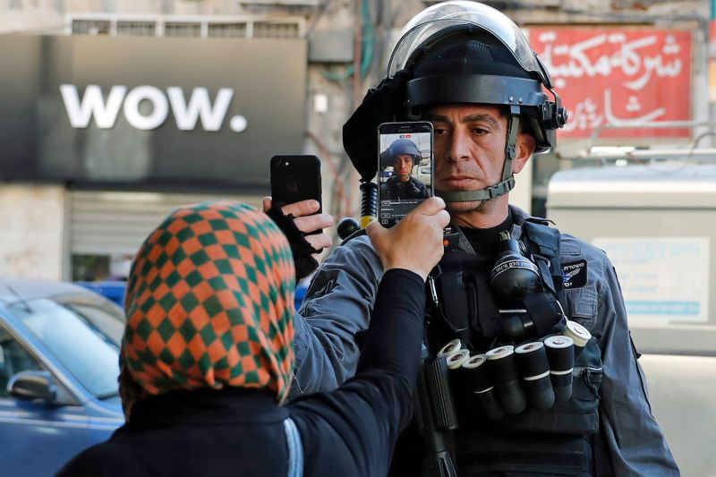 A Palestinian woman takes a picture of a member of the Israeli security forces as he takes her picture in a street in Jerusalem on December 16, 2017.