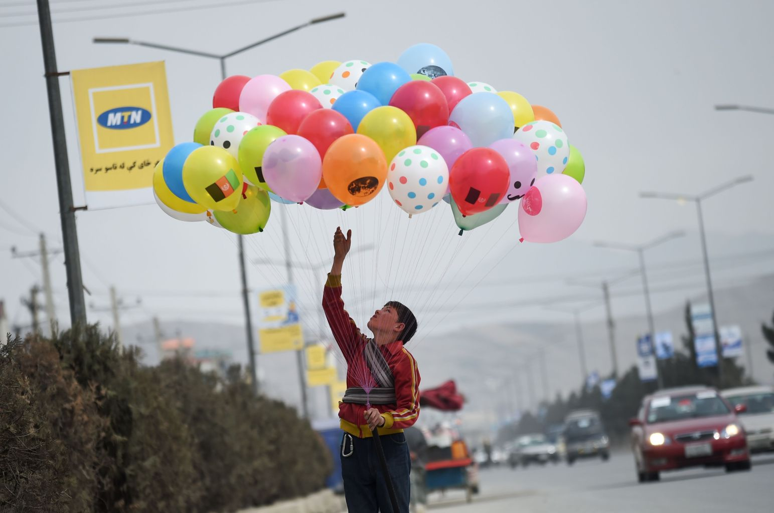 An Afghan child, who works as a balloon vendor, waits for customers alongside a street in Kabul on February 23, 2018. / AFP PHOTO / WAKIL KOHSAR        (Photo credit should read WAKIL KOHSAR/AFP/Getty Images)